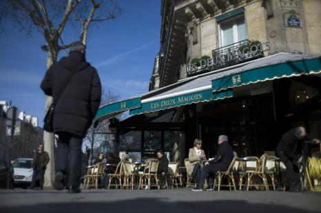 People have a drink at the terrace of 'Les Deux Magots' cafe in the Saint-Germain-des-Pres area,...
